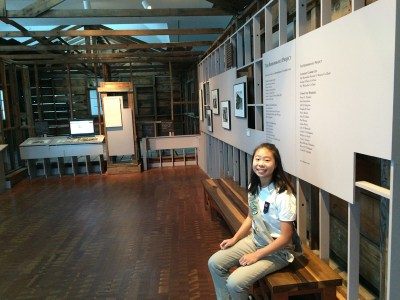 Ambassador Girl Scout Lauren Wong sits in front of JANM's Common Ground exhibition.