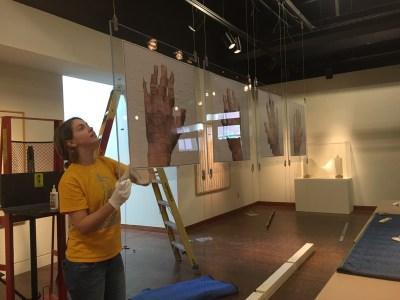 Christina lines up Paul Jackson's prints. Photo: Vicky Murakami.