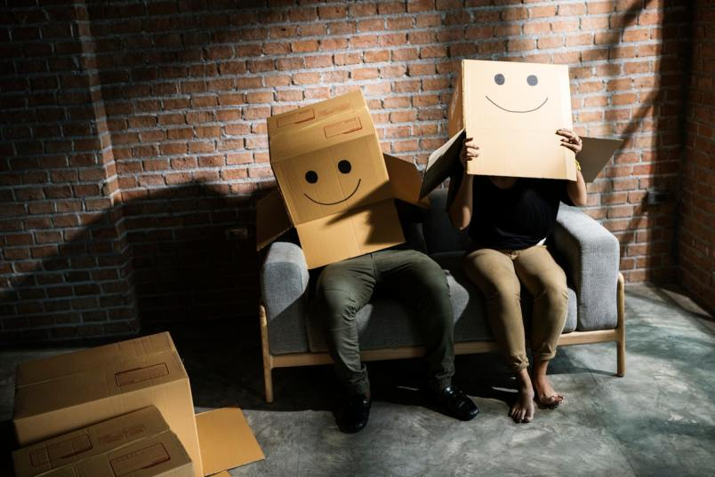 People with boxes with smiley faces on over their heads