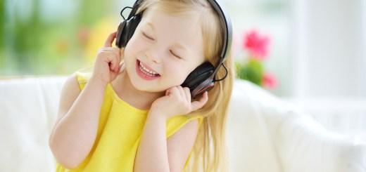 Cute little girl wearing huge wireless headphones. Pretty child listening to the music. Schoolgirl having fun listening to kid's songs at home. Home technology and music concept.