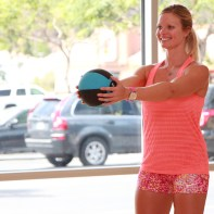 Danica performing a front shoulder raise using a medicine ball at LA Fitness - 2