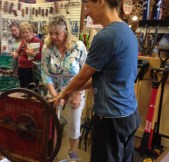 Karen and a guest use the antique corn sheller.