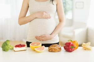 Health and unhealthy foods in front of pregnant Japanese woman