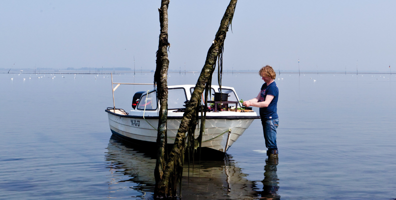 image of chef Bart van Olphen standing in shallow water, preparing food on bow of a boat
