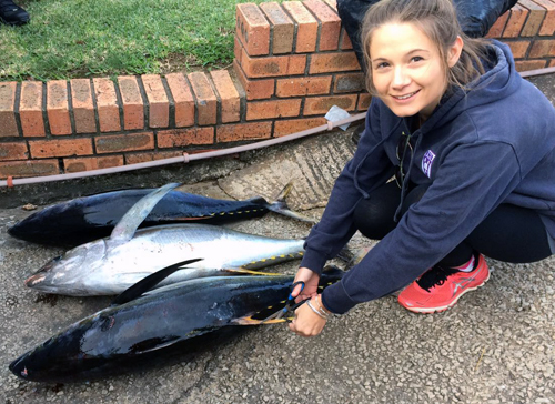 Woman crouching on ground with dead tuna cutting samples from fins