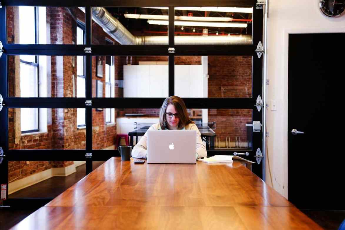 A young woman working on her MacBook at a long table in a stylish office