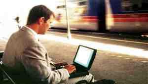 Mann hinter Klapprechner auf Bahnsteig