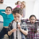 Caucasian family covering ears with boy playing recorder