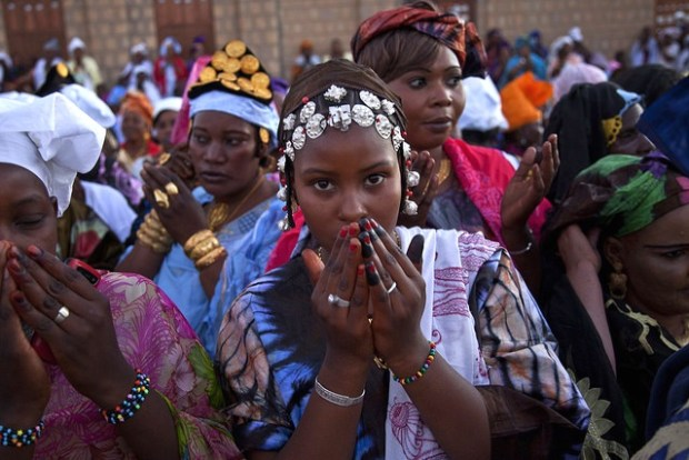 Scenes from the Maouloud Festival in Timbuktu, which was forbidden in 2013 during the Jihadist occupation. Women, wearing traditional clothes, pray outside the Sankore Mosque to celebrate the birth of the Muslim prophet, Muhammed. United Nations Photo /FLickr