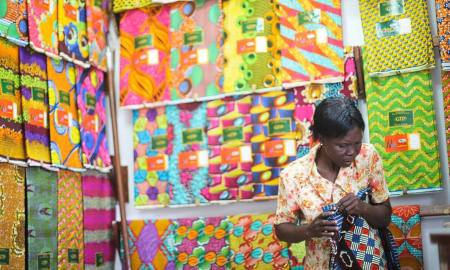 6 Colourful African Fabric Used Around the World_blog.swaliafrica.com_A trader measures a piece of GTP (Ghana Textile Print) cloth, by the yard, in her shop at Makola (mah-core-lah