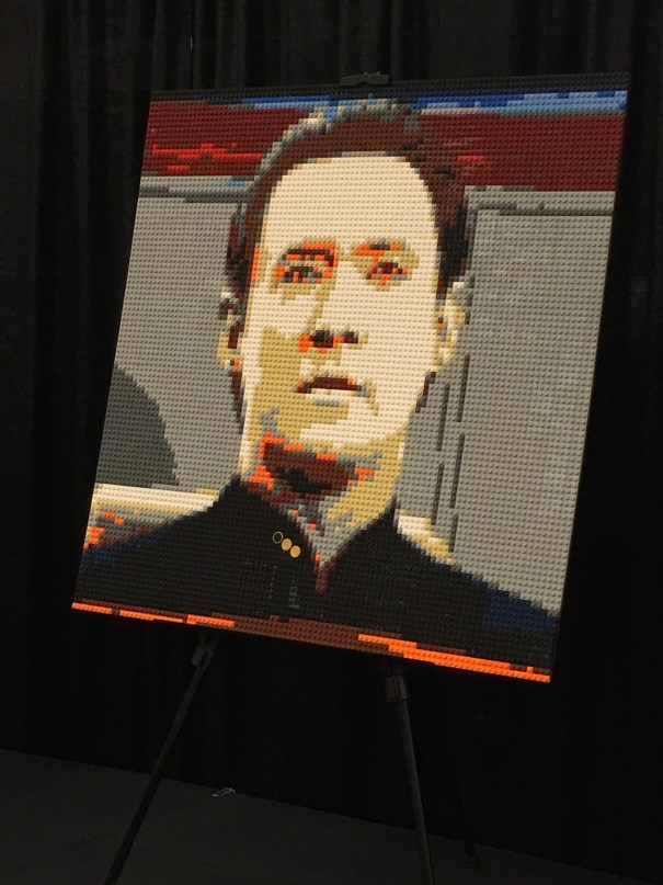 A portrait of Lt. Cmdr. Data, circa fourth season, made entirely out of colored Lego on a flat plate in a pixel art style.