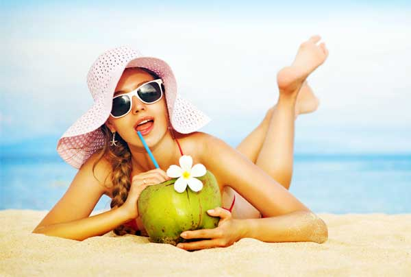 woman-beach-drinking-coconut