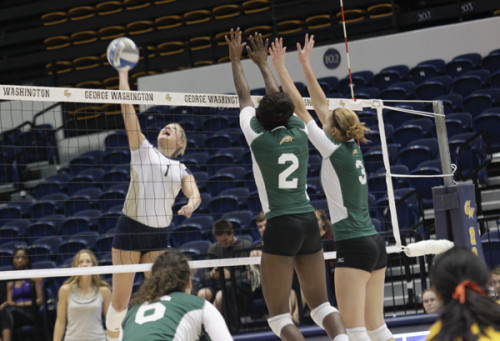 Senior outside hitter Rachael Goss hits the ball over the net in an October match against George Mason. Hatchet File Photo by Cameron Lancaster