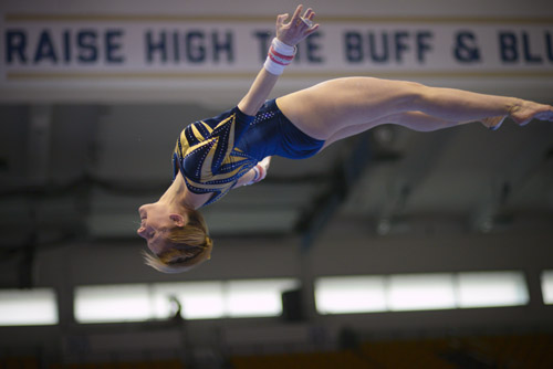 Junior Taylor Redmond goes airborne as she dismounts from the uneven bars.