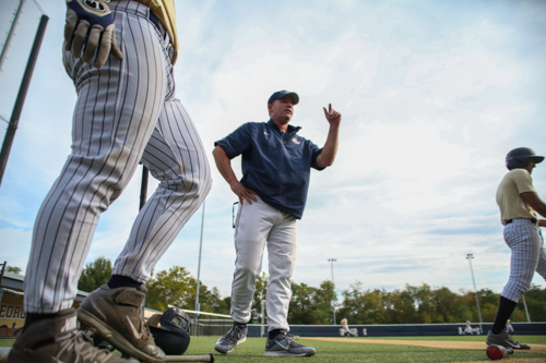 Head coach Gregg Ritchie speaks to his team during a batting practice this fall. Dan Rich | Contributing Photo Editor