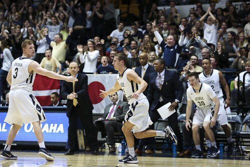 With head coach Mike Lonergan looking on, graduate student guard Alex Mitola celebrates after hitting a 3-pointer in GW's win against George Mason earlier this season. Dan Rich | Contributing Photo Editor