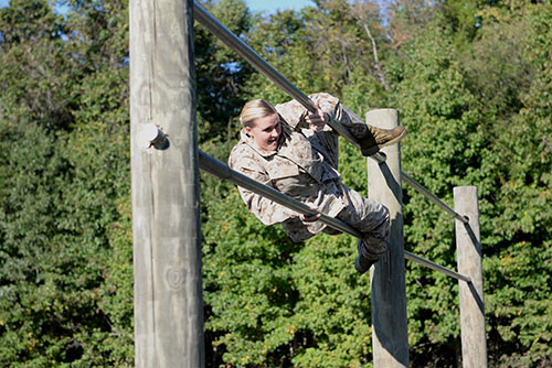 #10: Freshman Shelby Brown scales the double bars during the obstacle course. This rigorous, timed test requires midshipmen to maneuver over logs and climb ropes and metal poles.