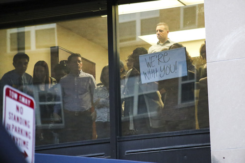 In the windows of Rice Hall, university employees gathered and drew a sign of support for the protest below. Keegan Mullen | Hatchet Photographer