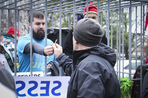 A volunteer inside a cage hands out a marijuana joint. DCMJ gave out more than 8,000 free joints Friday. Julia Abriola | Hatchet Photographer
