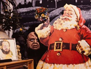 An illustrated cut-out Santa Claus propped beside a coffee table with Halloween masks and a painted backdrop