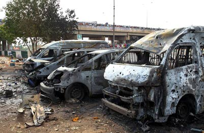 Burnt out vehicles at the scene of the Nyanya bus station explosions in Abuja Photo: Reuters