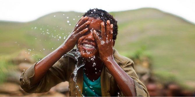 A boy splashes water onto his face