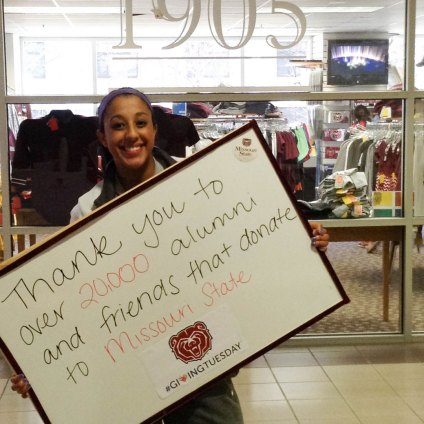 student with thank you sign for donations from alumni