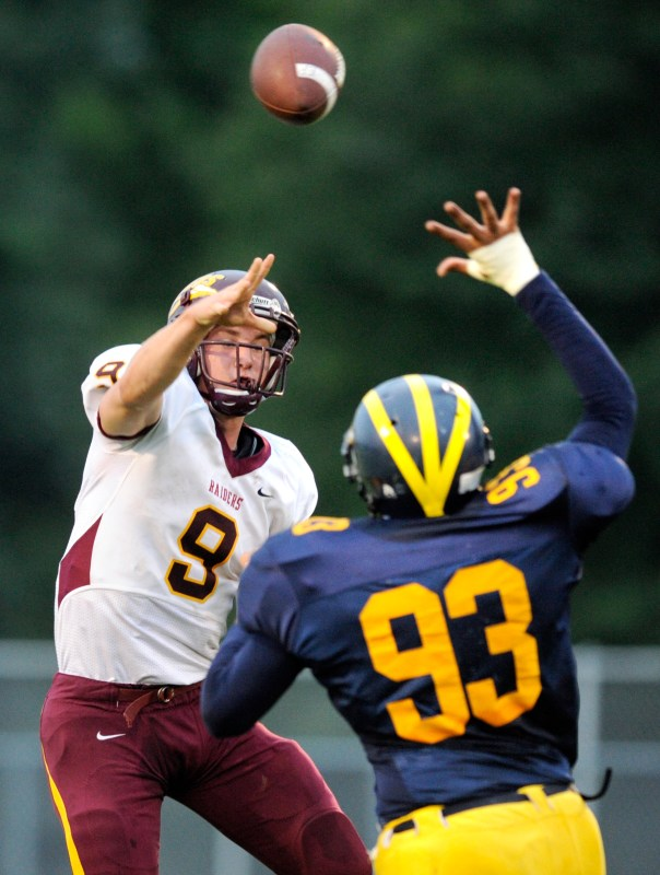 ADAM GERIK/JOURNAL STAR  East Peoria quarterback Caleb Eckhoff (9) throws a pass in front of Woodruff's Lindsay Harper (93) during Friday's game at Peoria Stadium.