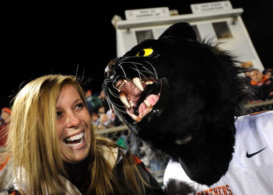 RON JOHNSON/JOURNAL STAR   Washington cheerleader coach Allison Minehan, left, laughs as student Jessie Westen, dressed as the Panther mascot, roars in her ear during Friday's game.