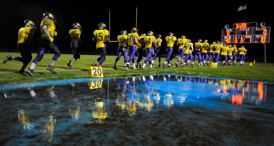 RON JOHNSON/JOURNAL STAR  Farmington players are reflected in a pool of rain water near the field as they run out onto the field before Friday night's game with Manual.
