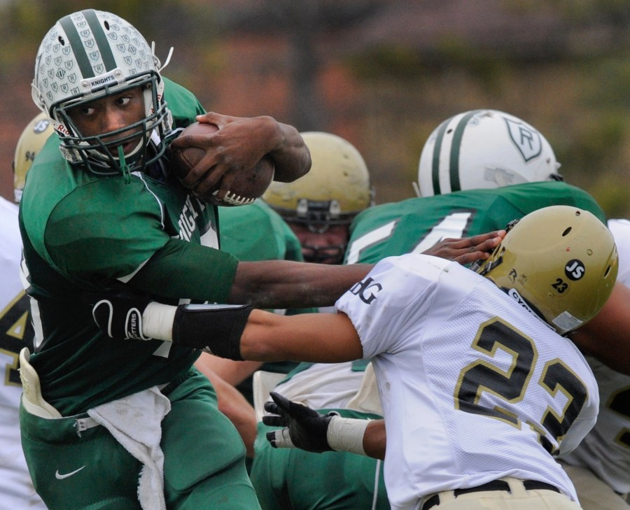 RON JOHNSON/JOURNAL STAR  Richwoods quarterback Mike Davis pushes cornerback Eddie Hubbard of Sacred Heart-Griffin out of his way on a run up the midd