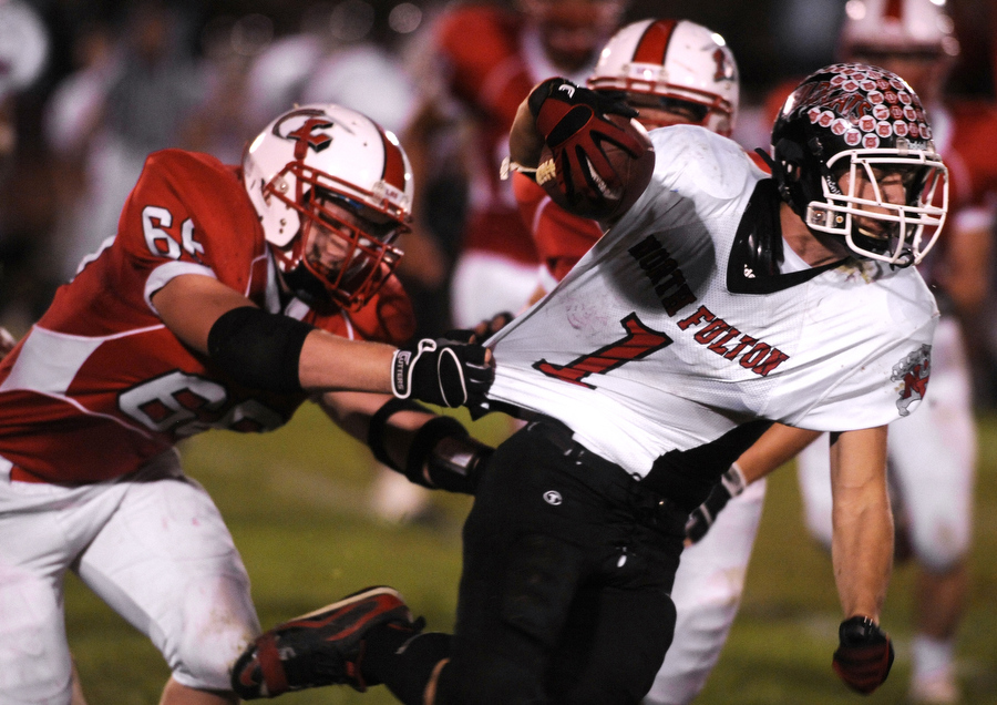 Lewistown's Chris Henzler, left, gets a handful of jersey as he tries to bring down North Fulton's John Davis IV during a game on Friday, Oct. 8, 2010, in Lewistown.