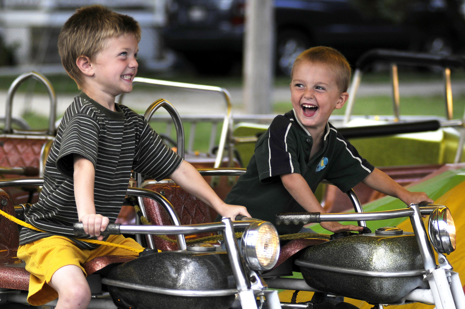 Brothers Matthew Williams, left, age 5, and Keaton Williams, age 3, share a few laughs as they ride motorcycles and honk the horns on a ride on Thursday, Sept. 9, 2010, at the Fall Festival in Elmwood, Ill.
