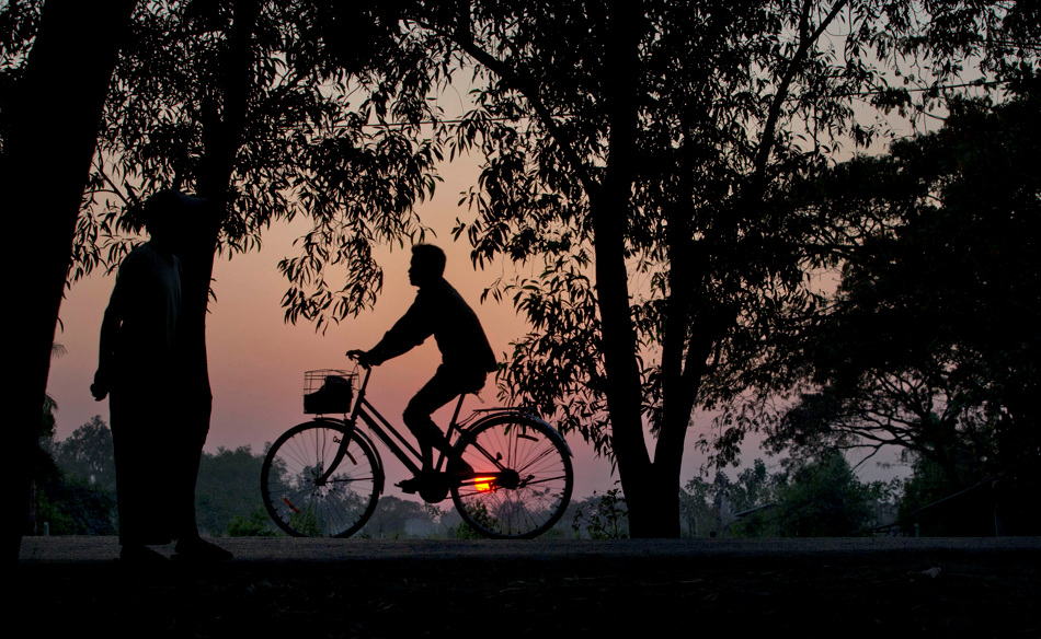 A man rides his bicycle as the sun sets in suburbs of Yangon, Myanmar, Monday, Feb. 4, 2013. (AP Photo/Gemunu Amarasinghe)