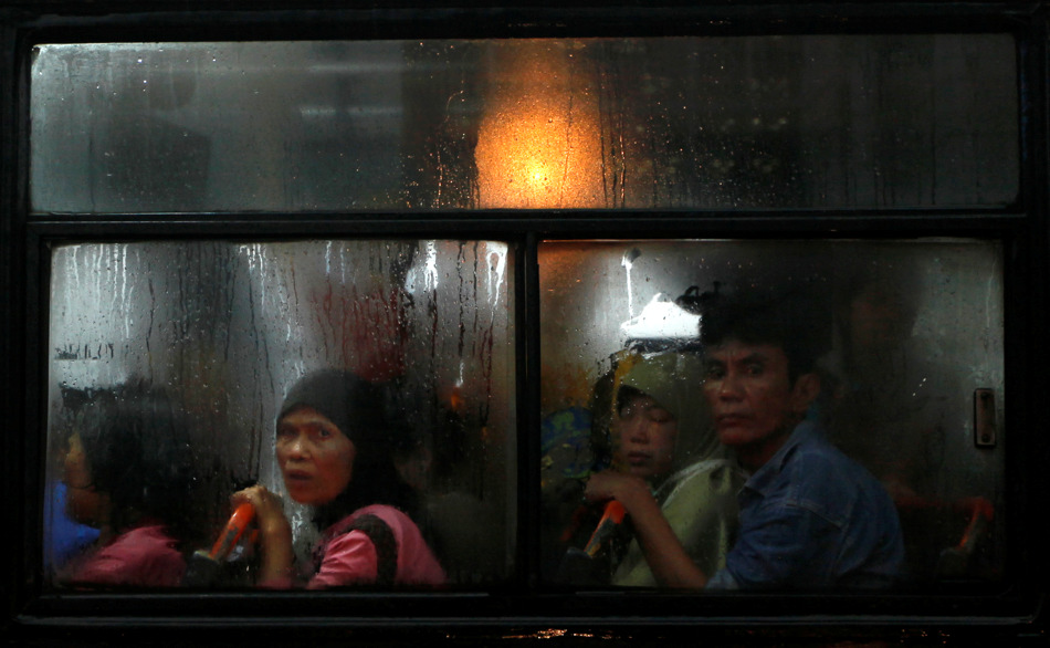 Passengers sit inside a bus stuck in a traffic jam following heavy rain at the main business district in Jakarta, Indonesia, Wednesday, Feb. 6, 2013. About an hour of torrential rain triggered knee-high floods on the main streets of the capital, causing heavy traffic jams. (AP Photo/Dita Alangkara)