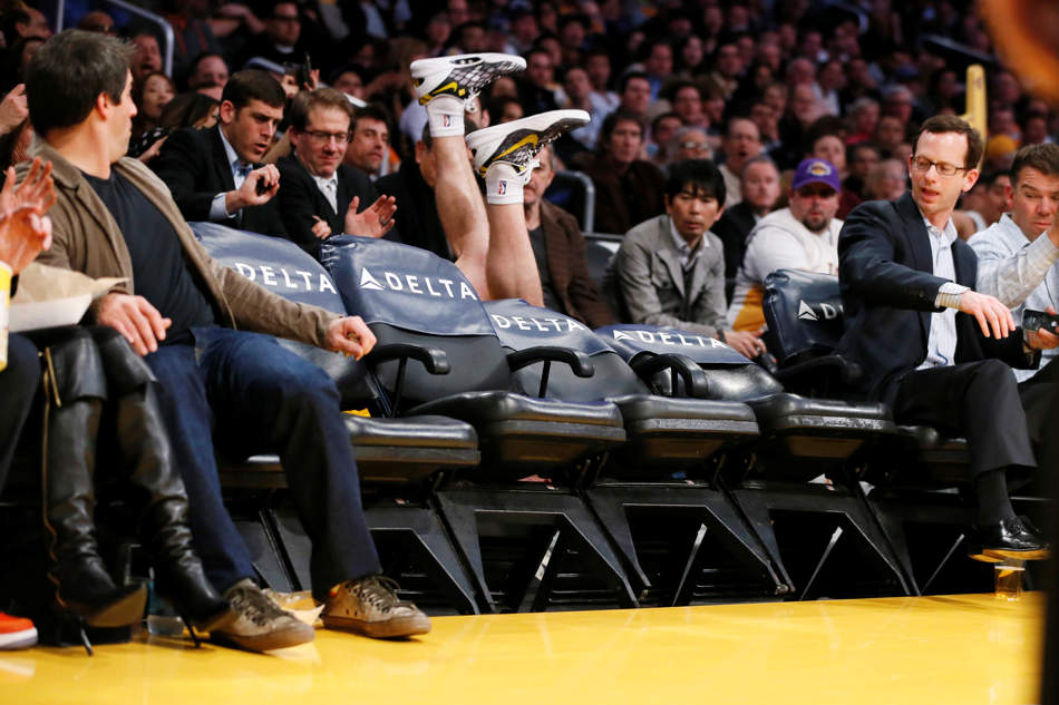 Los Angeles Lakers' Steve Blake falls over empty courtside chairs as he tries to save a ball from going out of bounds against the Phoenix Suns during the first half of an NBA basketball game on Tuesday, Feb. 12, 2013, in Los Angeles. (AP Photo/Danny Moloshok)