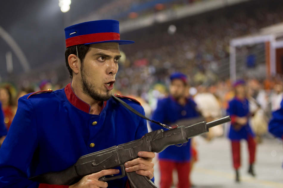 A dancer from the Nene da Vila Matilde samba school carries a toy gun as he performs during a carnival parade in Sao Paulo, Brazil, Saturday, Feb. 9, 2013. (AP Photo/Andre Penner)