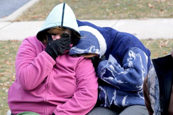 Two unidentified people shelter themselves from the below freezing temperatures after Pine Grove Grundsau Lodge No. 5's stuffed Groundhog Grover and his bride Sweet Arrow Sue predicted six more weeks of winter during the annual Groundhog Day Celebration in Pine Grove, Pa., Saturday, Feb. 2, 2013. (AP Photo/The Republican-Herald, Jacqueline Dormer)