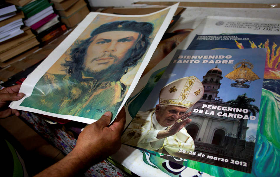 "A man holds an image of Cuban revolution leader Ernesto ""Che"" Guevara next to a poster printed during Pope Benedict XVI visit to Cuba last year at a bookshop  in Havana, Cuba, Monday, Feb. 11, 2013.  Pope Benedict XVI,  announced Monday that he's stepping down amid failing health. (AP Photo/Ramon Espinosa)"