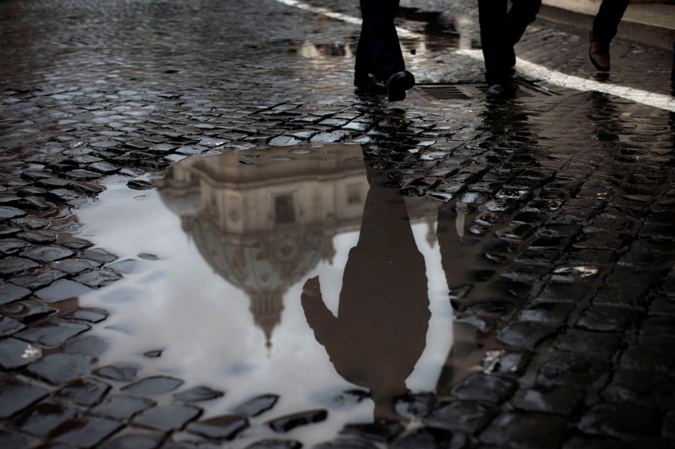 St. Peter's Basilica is reflected in puddle just during the second day of the conclave to elect a new pope, at the Vatican, Wednesday, March 13, 2013. Black smoke again billowed from the chimney of the Sistine Chapel on Wednesday, meaning that Catholic cardinals hadn't elected a pope on their second or third rounds of balloting. (AP Photo/Oded Balilty)