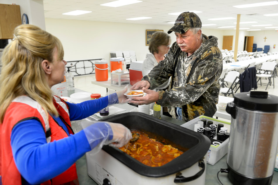 DAVID ZALAZNIK/JOURNAL STAR Ralph Atherton takes a dish of ravioli  Tuesday from Red Cross volunteer Julia Blankenship at the shelter set up at River's Edge United Methodist Church in Spring Bay.