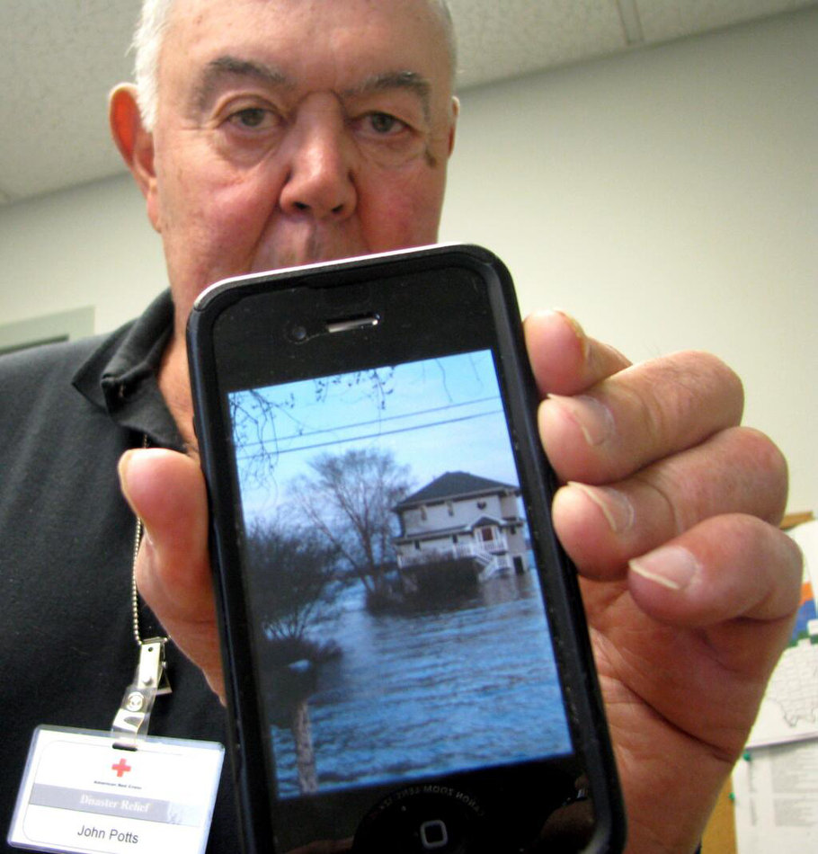 LAURA NIGHTENGALE/JOURNAL STAR John Potts of Rome works a twelve-hour shift Tuesday at the Red Cross while his home sits in four feet of water.