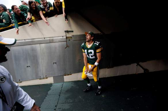 Green Bay Packers' Aaron Rodgers throws his towel to some fans after an NFL football game against the Washington Redskins Sunday, Sept. 15, 2013, in Green Bay, Wis. The Packers won 38-20. (AP Photo/Mike Roemer)
