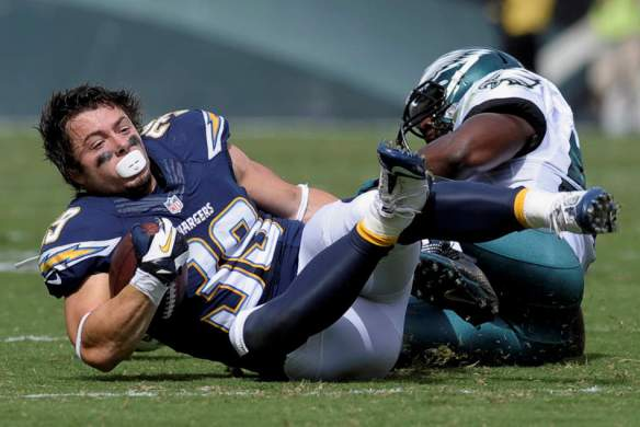 San Diego Chargers' Danny Woodhead, left, loses his helmet as he is tackled by Philadelphia Eagles' DeMeco Ryans during the first half of an NFL football game on Sunday, Sept. 15, 2013, in Philadelphia. (AP Photo/Michael Perez)