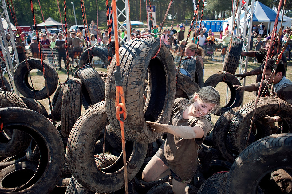 JUSTIN WAN/JOURNAL STAR Participants battle with car tires on Saturday morning during the last few rounds of Hard Charge obstacle race at Three Sisters Park in Chillicothe. The course featured more than 20 obstacles, including multiple challenges with mud pits.