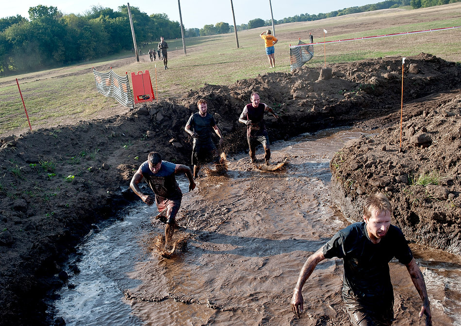 JUSTIN WAN/JOURNAL STAR Participants of the Hard Charge obstacle race run into a mud pit, Saturday morning at Three Sisters Park in Chillicothe.