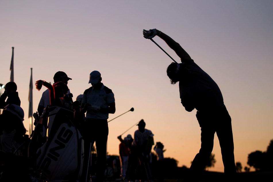 Golfers, seen in silhouette, warm up as the sun rises before the start of the second round of the Portugal Master golf tournament at the Victoria golf course in Vilamoura, southern Portugal, Friday, Oct. 11, 2013. (AP Photo/Francisco Seco)