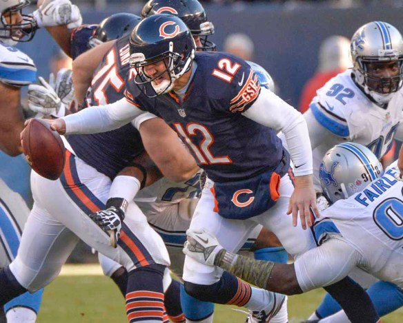 Bears quarterback Josh McCown tries to break the tackle of the Nick Fairley of the Lions.