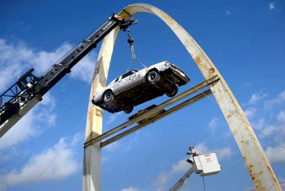 DAVID ZALAZNIK/JOURNAL STAR  A crane lifts a 1982 Buick Regal from its perch on the Neal's Auto Parts, Inc. arch on Nov. 7 on Farmington Road where it has been bolted in place since 1987. The arch will be cleaned and painted and the platform loaded with a replacement car.