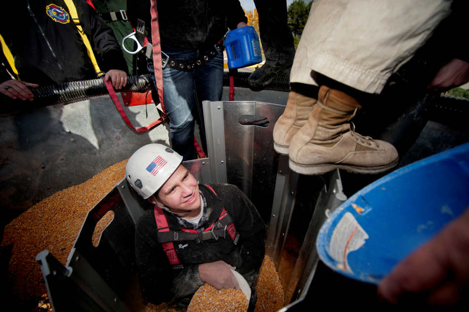 JUSTIN WAN/JOURNAL STAR Ryan Schrock of Metamora, who volunteered to be trapped inside a grain bin rescue simulation device, watches as another training participant adjusts the height of a rescue device on Nov. 2 at Jump Trading Simulation & Education Center.